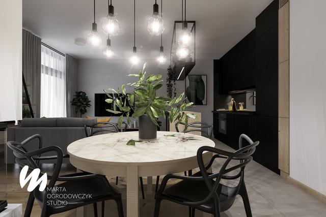 Salon z czarną kuchnią